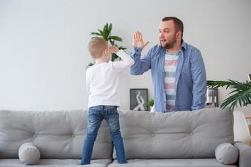 Family photo of young son standing on couch doing handshake with father