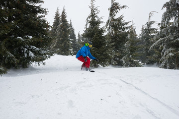 Snowboarder, preparing to jump, while rides down a mountain slope