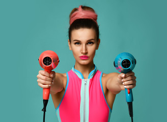 Happy young brunette woman with hair dryer on blue mint background