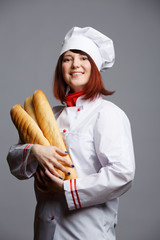 Photo of woman cook in white robe and cap with loaves