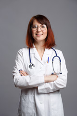Image of smiling brunette doctor in white coat and with phonendoscope in glasses