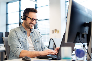 Young smiling male call center operator doing his job with a headset.Portrait of call center worker at office.