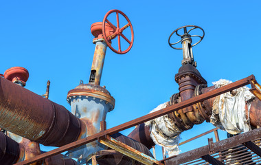 Old rusty pipeline with valves against the blue sky background