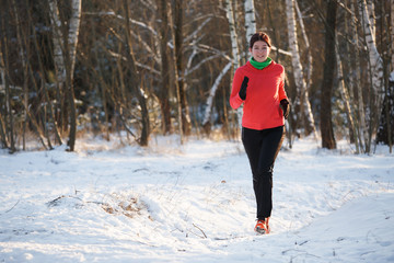 Photo of sports girl on run through winter forest