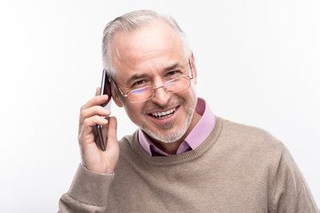 Nice chat. The close up of a handsome grey-haired senior man in eyeglasses talking on the phone and smiling at the camera while posing isolated on a white background