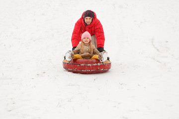 Photo of father and daughter on walk with tubing in winter park