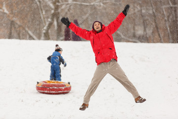 Photo of happy father and son on winter walk with tubing
