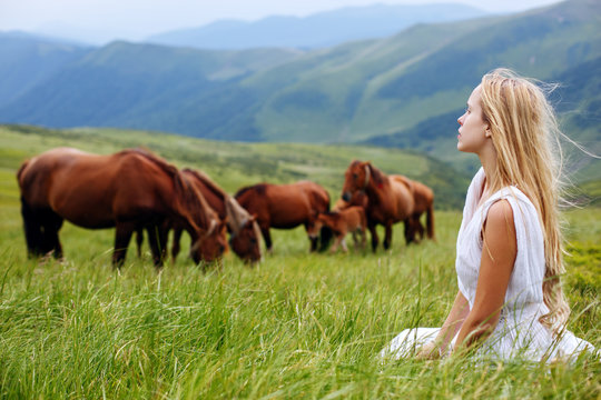 Woman sitting on mountain top and contemplating the sunset. Beautiful woman and horses in the mountains. Romantic young beauty with a horse. Young woman in a long white dress