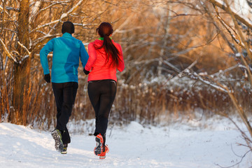 Image from back of sports woman and man running on winter