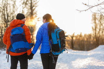 Image from back of man and woman with backpacks in winter forest