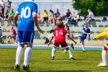 Running Soccer Football Players. Soccer Kick; School Football Game. Footballers Kicking Football Match; Young Soccer Players Kicking Ball. Footballers in Jersey Shirts. Spectators in the Background