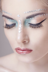 Fantasy make-up in pastel colors and with rhinestones in the closed eyes close-up