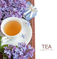 Tea cup with lilac bunch, cakes and gifts isolated on white background