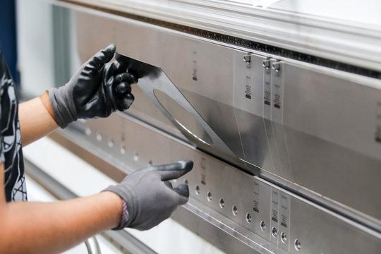 Worker operator bending metal sheet process by sheet bending machine for bus manufactuing part, steel folding with machine.