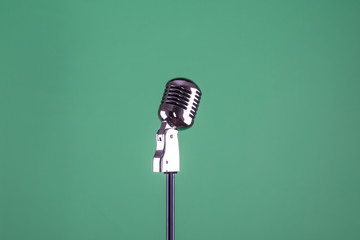 vintage microphone on a green isolated background