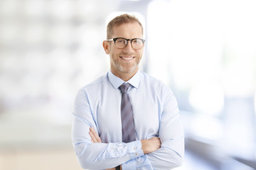 Executive businessman at the office. Smiling senior investment advisor business man wearing shirt and tie while standing at the office and looking at camera. Wall mural