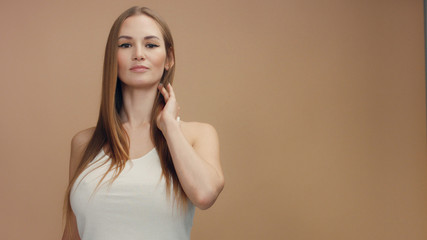 beauty woman model in studio on beige background touches her straight blonde hair and watching at camera