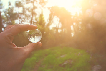 male hand holding small crystal globe. travel and global issues concept.