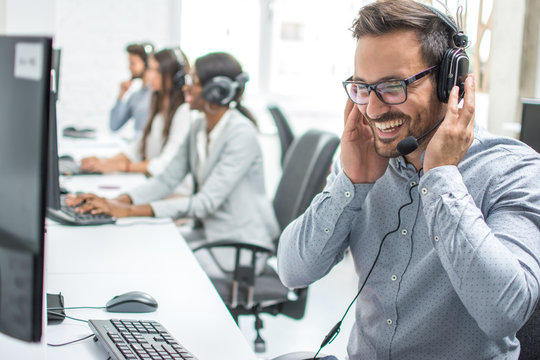 Smiling customer service executive with headset working in call center.