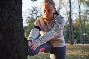 Curvaceous young woman training in park, touching toes against tree trunk