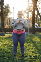 Curvaceous young woman training in park, looking at smartphone