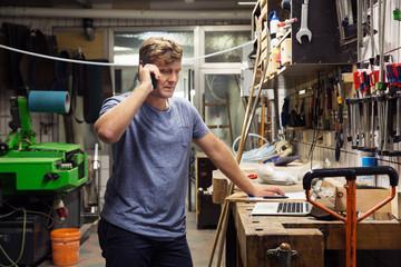 Man in workshop, using smartphone, looking at laptop