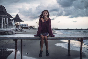 Portrait of young woman sitting on pier at dusk, Odessa Oblast, Ukraine