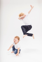Portrait of boy leaping in air over baby brother