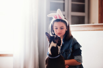 Girl sitting with dog, indoors, girl wearing Easter bunny ears