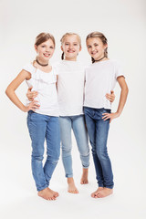 Studio portrait of three girls posing with hands on hips