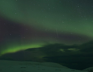 Aurora borealis over snow covered landscape at night, Finnmark, Norway