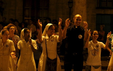 A priest and nuns gather during a prayer vigil in front of Havana's cathedral