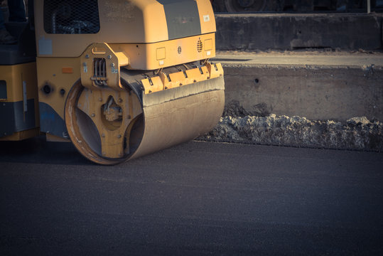 Side view small yellow ride on roller asphalt compactor aligns the road. Laying new asphalt. Vibration roller compactor. Vintage tone.