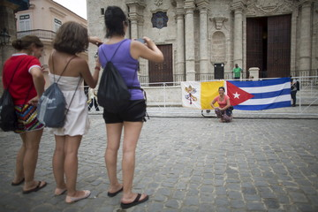People take pictures with the Vatican and Cuban flags in front of the The Cathedral of The Virgin Mary of the Immaculate Conception in Havana