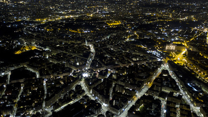 Panoramic night aerial view of the Tuscolana district, in the city of Rome in Italy. The streets and buildings are illuminated by street lamps and car headlights.