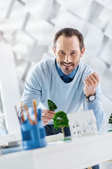 Feeling happy. Attractive cheerful dark-haired bearded man smiling and constructing the model of a house while standing at the table