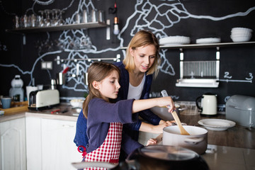 A small girl with her mother cooking at home.