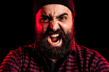 Angry screaming bearded man on black background with two red lights in the back
