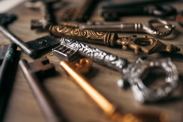 Many vintage keys in the defocus on a wooden background
