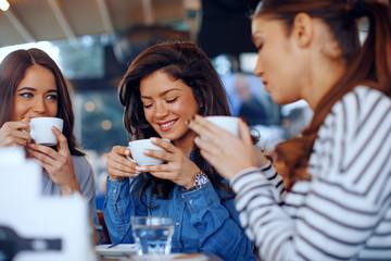 Three young women enjoy coffee at a coffee shop