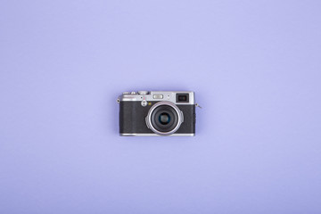 Old fashioned rangefinder camera on purple background, flat view