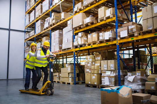 Two young workers in a warehouse.