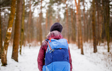 Image from back of walking woman with backpack over winter forest