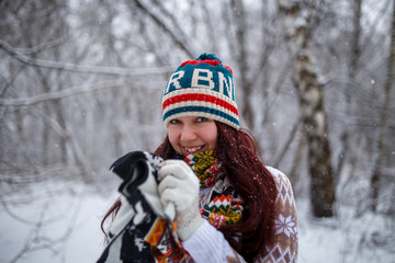 Photo of smiling brunette in knitted cap and scarf in winter forest during day