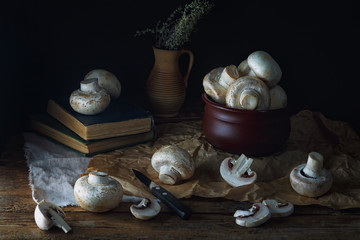 ...Mushrooms champignons on an old rustic wooden table on a dark background. Low key. Focus concept. .Vintage style....