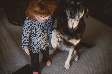 Young girl standing beside pet dog, holding dog's paw