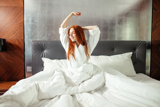 Redhead Woman stretching in bed after waking up, entering a day happy and relaxed after good night sleep
