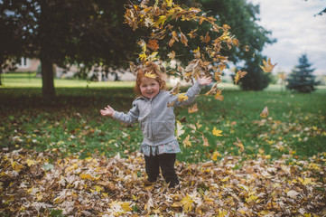 Portrait of red haired female toddler in park throwing autumn leaves