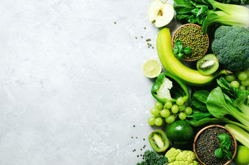 Organic green vegetables and fruits on grey background. Copy space, flat lay, top view. Green...