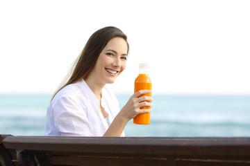Woman holding an orange juice bottle on the beach